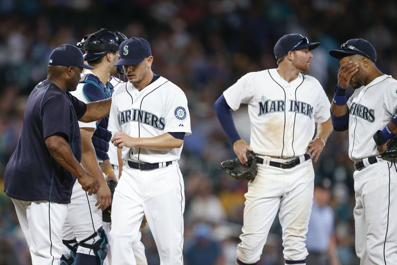 Mariners pitcher Rob Rasmussen, third from left, leaves the mound after failing to get an out in the 11th. (Associated Press)