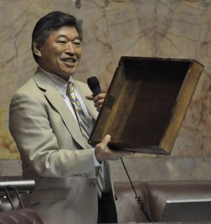 OLYMPIA -- During a lull in legislative activity, State Sen. Bob Hasegawa, D-Seattle, holds up his desk drawer to read out the names of previous occupants of his desk on the floor of the Senate. (Jim Camden/The Spokesman-Review)