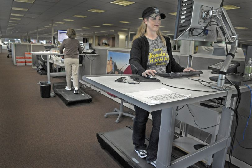 Pitney Bowes service and field-support agent Jenni Lindsey, right, and purchase power agent Sandy Epps work on walking stations at the company call center in Spokane on Tuesday. The upright stations feature a slow-moving treadmill and are in high demand by employees who prefer to stand while working. (Christopher Anderson)