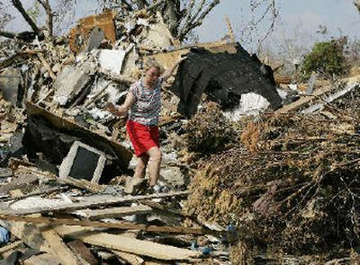 Christine Ross of Waveland, Miss., walks through what's left of her home on Sunday after it was destroyed by Hurricane Katrina.   (Associated Press / The Spokesman-Review)