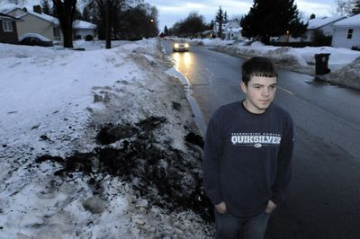 Joshua Myers stands Wednesday where a van crashed and burned  Tuesday near his home on North Belt Street in Spokane. Myers managed to break out a window and pull the driver to safety.  (Jesse Tinsley / The Spokesman-Review)