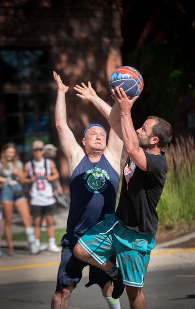 Jeff Taylor, left, tries to block a shot by Tony Kopp during the Hoopfest 3-on-3 basketball tournament in downtown Spokane on Saturday, June 29, 2019. Taylor and other players on his Hoopfest team, Against the Grain, are formerly homeless. (Colin Mulvany / The Spokesman-Review)