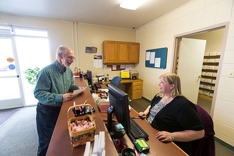 Dan English, former Kootenai County Clerk and a registered democrat, turns in a form to change his affiliation, allowing him to vote in the republican primary, to clerical employee Grace Studer Thursday at the Kootenai County Elections Office in Coeur d���Alene. (Shawn Gust/press)