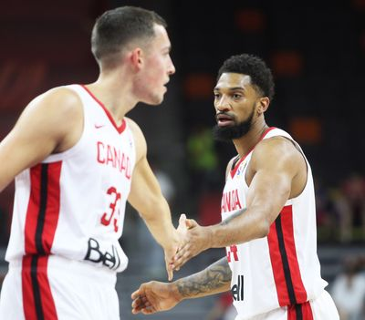 Kyle Wiltjer (left) is congratulated by teammate Khem Birch during Canada's group H match against Senegal in the 2019 FIBA Basketball World Cup 2019.  (Associated Press)