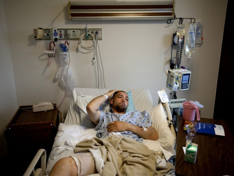 Jesse Hugh Johnson scratches his head as he lies with a bandaged thigh in a hospital bed on Monday at Providence Sacred Heart Medical Center in Spokane. Johnson was shot in the leg by a Spokane police officer while armed with what turned out to be a BB gun. (Tyler Tjomsland)