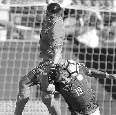 Costa Rica's Johnny Acosta, top, and Paraguay's Dario Lezcano  collide during Saturday's Copa America  soccer match. (Stephen M. Dowell / Associated Press)