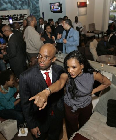"""Maggie Anderson talks with Michael Hill while they prepare for a presentation of """"The Empowerment Experiment"""" at the black-owned Vino Libro wine bar in Atlanta. Anderson and her husband are founders of the movement in which people pledge to only patronize black-owned businesses for a year. (Associated Press / The Spokesman-Review)"""