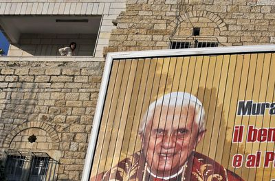 A Palestinian woman in the West Bank town of Bethlehem stands next to a rotating banner showing Pope Benedict XVI. The pope will visit Israel and the West Bank during a five-day tour.  (Associated Press / The Spokesman-Review)