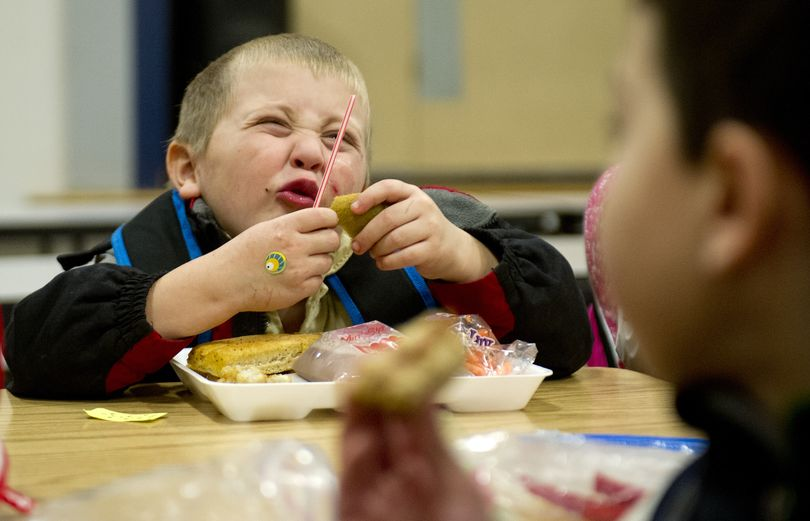 Joshua Bailey, 5, enjoys a kiwi during lunch with fellow kindergartners on Wednesday at Broadway Elementary in Spokane Valley. (Tyler Tjomsland)