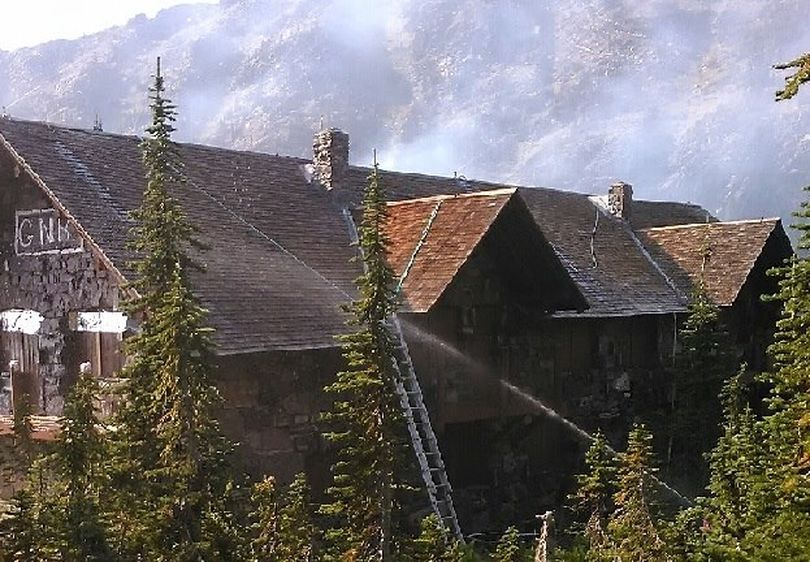 Firefighters work to save the 103-year-old Sperry Chalet from a wildfire in Glacier National Park on Aug. 27.  On Aug. 30, despite their efforts, the main structured caught fire and burned. (National Park Service)