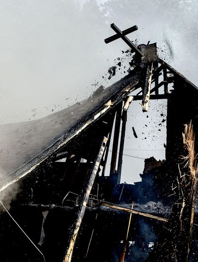 A cross made of steel breaks loose as crews continued to battle the arson blaze at St. Ann's Catholic Church in Bonners Ferry on Thursday, April 21, 2016. (Kathy Plonka / The Spokesman-Review)