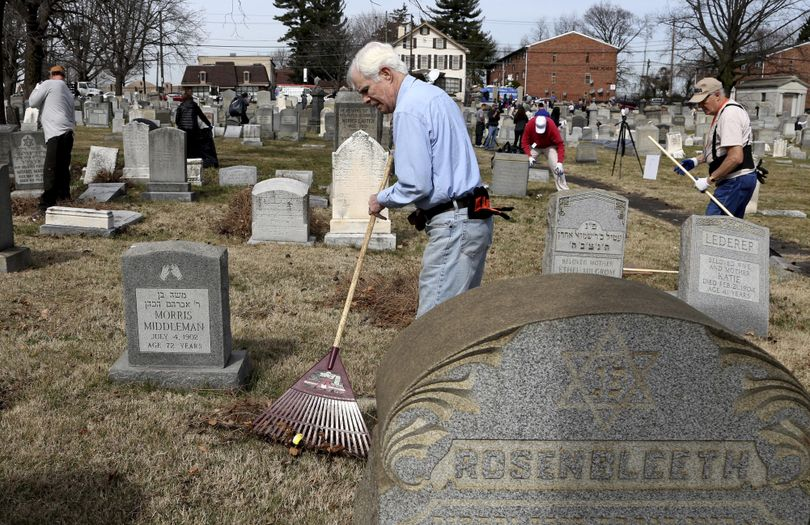 Volunteer John Walsh from northeast Philadelphia rakes debris at Mount Carmel Cemetery on Tuesday, Feb. 28, 2017, in Philadelphia. (Jacqueline Larma / Associated Press)