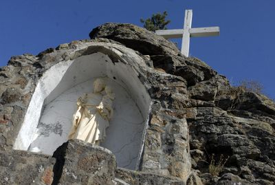 The statue of St. Joseph and a 10-foot wooden cross emerge from the basalt outcroppings that rise high over the headstones and lawn above  St. Joseph's Catholic Cemetery off Trent Avenue in Spokane Valley.  (J. BART RAYNIAK / The Spokesman-Review)