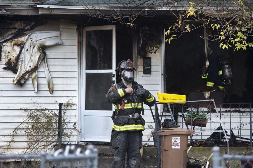 Spokane Fire Department crews work the scene of a fatal house fire at 1227 E. Longfellow Ave. on Tuesday morning. (Dan Pelle)