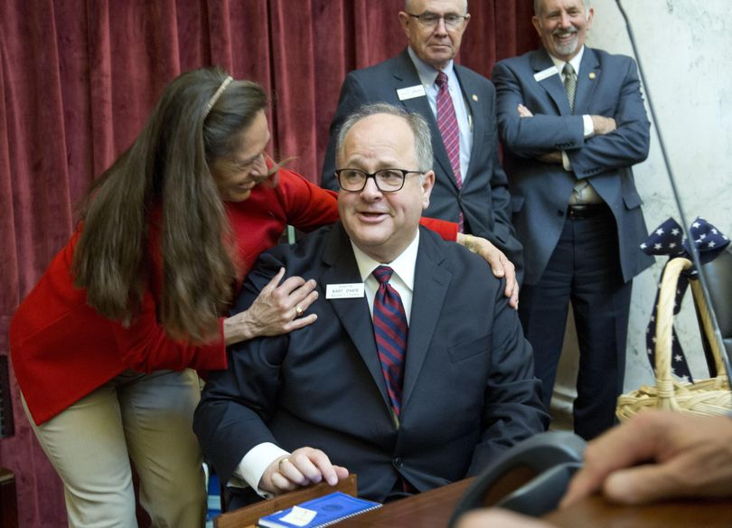 Senate Minority Leader Michelle Stennett, D-Ketchum, left pays tribute to Sen. Bart Davis, R-Idaho Falls, center, after the Idaho Senate adjourned for the year on March 29, 2017. Davis, who has served in the Senate for 19 years and as its majority leader for the past 15 years, was confirmed Thursday as the next U.S. Attorney for Idaho. (Katherine Jones / AP)