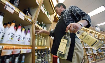Bill Oldenburg stacks shelves at a Seattle state-run liquor store.  The state is moving aggressively to capitalize on liquor sales.  (Associated Press / The Spokesman-Review)