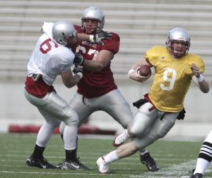 Washington State quarterback Kevin Lopina looks for running room as Joe Eppele blocks Cory Mackay, left. Special to  (Tyler Tjomsland Special to / The Spokesman-Review)