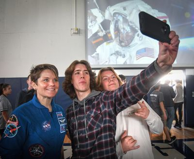 NASA astronaut and Gonzaga Prep grad Anne McClain has a picture taken with G-Prep juniors Timmy Craven and Liam Arnold after an assemble at the school, Thursday, Oct. 10, 2019, in Spokane, Wash. (Dan Pelle / The Spokesman-Review)