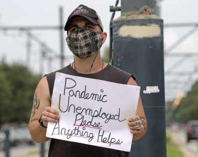 Sean Harris holds a sign asking for help while standing on the neutral ground on Carrollton Ave. at Bienville Ave. in New Orleans, Friday, Sept. 4, 2020. Harris had just completed training to be a hunted history tour guide in the French Quarter when the coronavirus pandemic hit. He has not been able to find a job since.  (Associated Press)