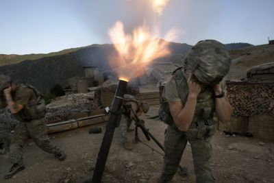 Soldiers from the U.S. Army First Battalion, 26th Infantry fire mortars from the Korengal Outpost at Taliban positions in the Korengal Valley of Afghanistan's Kunar province on Tuesday. (Associated Press / The Spokesman-Review)