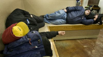 Men doze after lunch Wednesday at the House of Charity in Spokane. The shelter, which also serves as an emergency warming center, has seen an increase in the numbers of homeless people seeking assistance.  (Colin Mulvany / The Spokesman-Review)