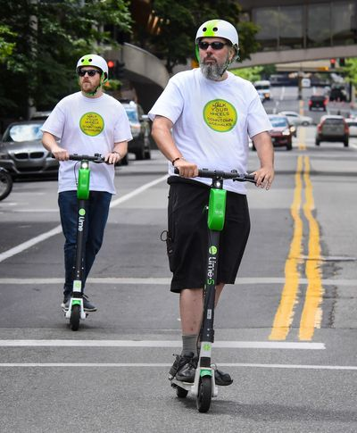 Lime employees Kelly Lotze and James Langford ride on Howard Street during the kickoff of the Lime Patrol in June 2019.  (DAN PELLE)