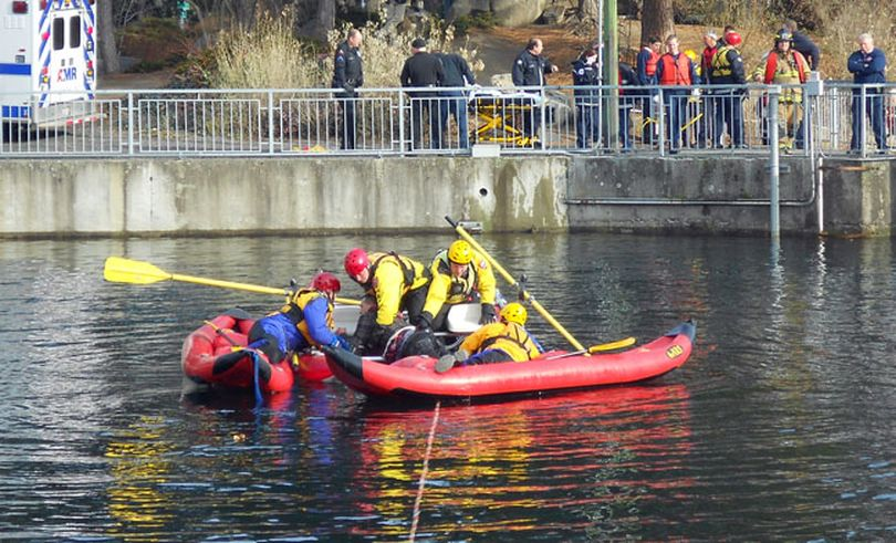 Crews rescue a man from the Spokane River in Riverfront Park today. (Meghann Cuniff / The Spokesman-Review)