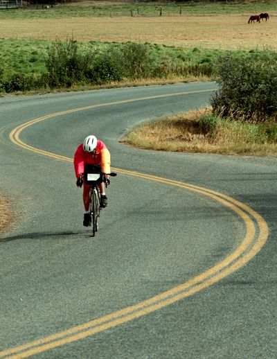 Barb Brucker of Seattle bikes along West Hauser Lake Road in Post Falls during the Tour des Lacs two-day ride in September.