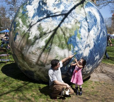 Ram Khadka shows his daughter, Roselyn, 3, a location along the coast of Japan as the pair visit Earth Day 2015, April 18, in Spokane's Riverfront Park. (Dan Pelle / The Spokesman-Review)