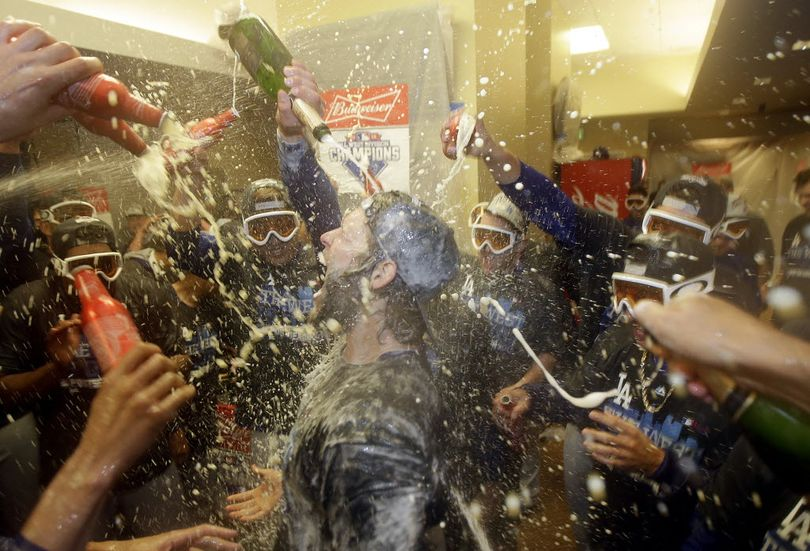 Los Angeles Dodgers pitcher Clayton Kershaw, center, celebrates with teammates in the locker room after the Dodgers beat the San Francisco Giants in a baseball game in San Francisco, Tuesday, Sept. 29, 2015. The Dodgers won 8-0 to clinch the National League West division. (AP Photo/Jeff Chiu)