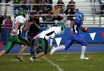 Coeur d'Alene's Kevin Ah-Hi breaks free from East Valley's Jake Labelle, left and Jye Lanphere for the first of his three 50-plus-yard touchdown runs Friday night at Coeur d'Alene High School.  (Tom Davenport/ / The Spokesman-Review)