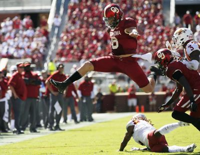 In this Oct. 7, 2017 photo, Oklahoma quarterback Baker Mayfield (6) leaps over Iowa State defensive back De'Monte Ruth, bottom, in the second quarter of an NCAA football game in Norman, Okla. (Sue Ogrocki / Associated Press)