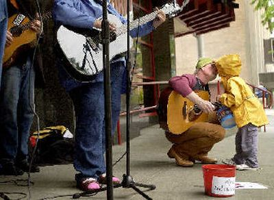 For the love of charity – Benjamin Lyons, 4, kisses his dad, Jim, Tuesday afternoon in downtown Spokane while a group of musicians, including the Lyons duo – dad on guitar and Benjamin on drums – play to raise money for the Second Harvest Food Bank.   (Brian Plonka / The Spokesman-Review)