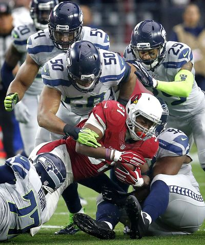 K.J Wright (50) and Seattle's top-rated defense, here putting the clamps on Arizona running back David Johnson, will be tested by Atlanta's top-rated offense Sunday in Seattle. (Rick Scuteri / Associated Press)