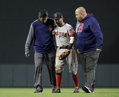 Boston Red Sox second baseman Dustin Pedroia, center, is assisted off the field after being injured during the eighth inning of the team's baseball game against the Baltimore Orioles in Baltimore, Friday, April 21, 2017. (Patrick Semansky / AP)