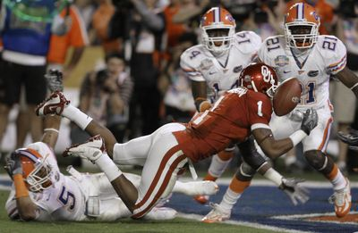 Oklahoma's Manuel Johnson (1) can't make the catch on a throw from Sam Bradford, which Florida's Major Wright (21) intercepted. (Associated Press / The Spokesman-Review)