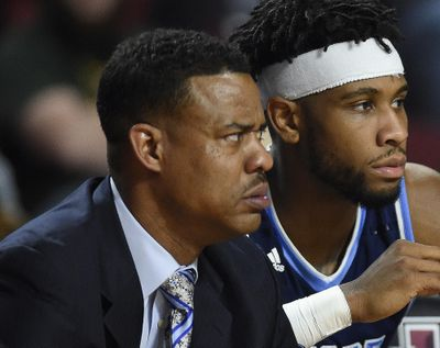 In this Jan. 30, 2018 file photo, Rhode Island associate head basketball coach David Cox, left, sits on the bench during an NCAA college basketball game in Amherst, Mass. Rhode Island announced Wednesday, April 4, 2018, it had promoted Cox to be the men's basketball coach. He served as associate head coach for the last four years under Dan Hurley, who left in March to become head coach at UConn. (Jessica Hill / Associated Press)