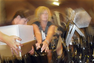 Melody Padrta tries to keep up with the bottling line Friday at Grande Ronde Winery.  (CHRISTOPHER ANDERSON / The Spokesman-Review)